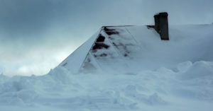 Snowy roof peaking out over high snow.