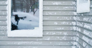 Recent snow clings to home siding and window frame.