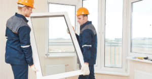 Workers carry a replacement window into a room.