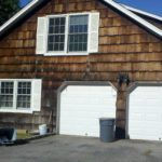 before construction photo showing old and rotten wood shingle and garage, driveway view